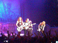 Iron Maiden guitarists in concert depicting the synchronization of guitars