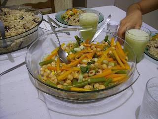 No centro da mesa, salada colorida de grão-de-bico, cenoura, vagem, milho, azeitonas, pepino e hortelã, rodeado de copos com suco e pratos.