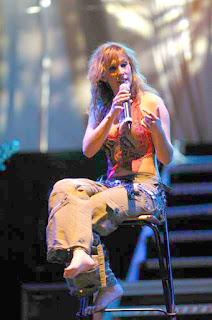 La cantante española Malú, se dirige a su publico sentada descalza sobre un taburete