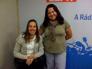 No estúdio da Eldorado, Mara ao lado de Bianca, que usa uma blusa verde e cachecol e sorri ao ser fotografada