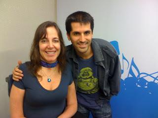 Mara ao lado de Cris Borges,  que está sorrindo e  apoiado no ombro da apresentadora. Ele veste camiseta e blusa azul, tem cabelo e olhos castanhos