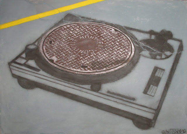 Montreal Conduits manhole cover on the road with a spray painted turntable creating illusion of sewer as the record.