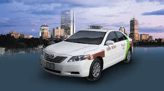 Image of Toyota Camry Hybrid Boston Cab with Boston skyline behind it