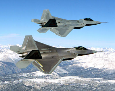 Two US F-22 Raptors flying in formation over snow-covered mountains