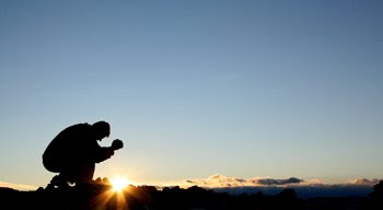 Man kneeling in prayer as the sun rises behind him.