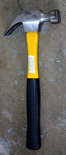 A yellow-handled claw hammer