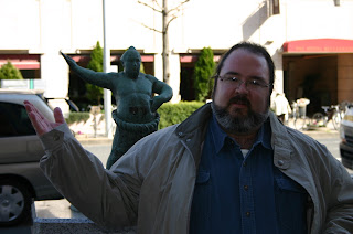 Jonathan Eller in front of a statue of a Sumo wrestler
