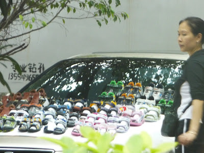 Street Hawker selling shoes on car bonnet in Shenzhen
