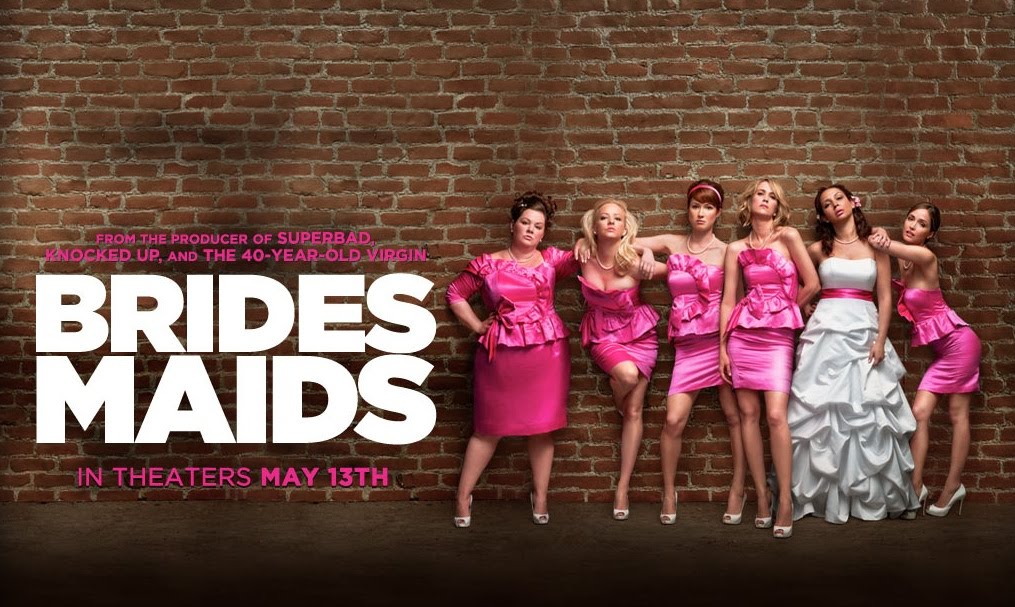 Bridesmaids poster: All the cast leaning against a wall in pink dresses