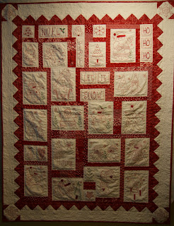 Three RedWork Quilts on a clothesline in the Garden.