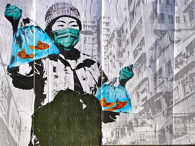 photo of street art in which an apparently Chinese woman is carrying bags of goldfish with a background that appears to be Hong Kon
