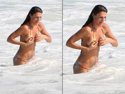 Luciana Costa faz topless na praia e paga peitinho
