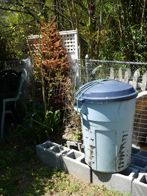 garbage can compost tumbler on blocks