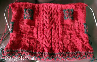 Ett halvt stickat bakstycke till en norsk-tröja i rött och svart garn.