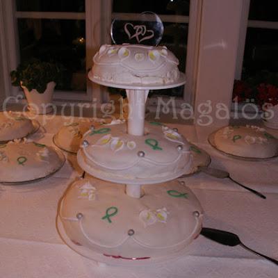 Tre våningar bröllopstårta med vit marsipan och vita kallor på. Ett stort glashjärta på toppen med inristade hjärtan.