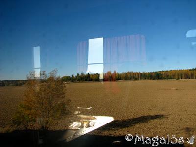 Foto taget genom tågfönstret, med motstående fönster som speglar sig i mitt fönster. Även bordet med vinglaset speglas i mitt fönster.