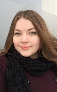 Kuva Reta Anna Mariasta. Hänellä on ruskeat pitkät hiukset, vaalea iho ja neutraali meikki. Hänellä on päällään tummanpunainen villakangastakki ja musta neulottu huivi. Hänen ilmeensä on hiukan viekas.