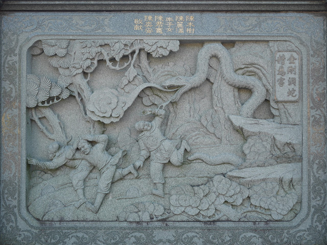 stone carving of scene of three men fleeing a very large snake in a tree