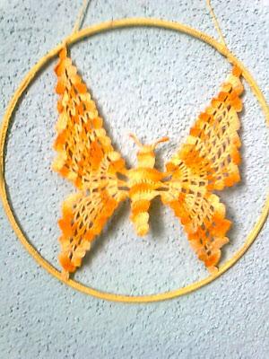 Szydełkowy moty. w kolorze żółtego melanżu w metalowej obręczy. Obręcz obrzucona szydełkiem również żółtym kolorem