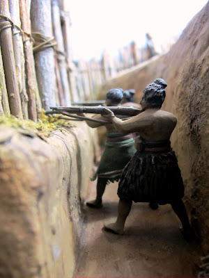 Diorama of Maori with muskets in a trench, defending a pa.