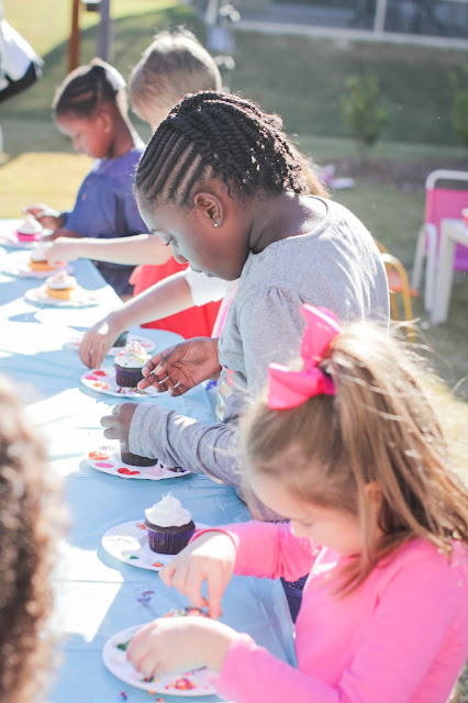 Girls decorating cupcakes at a Rainbow Party or an art party