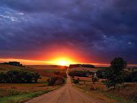 Gün batımı ufkuna doğru uzanan uzun toprak bir yol