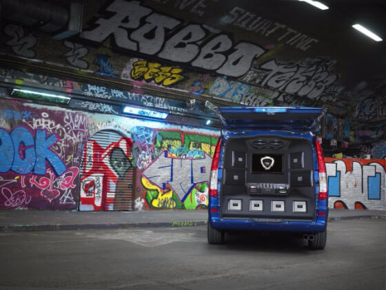 Van loaded with woofers and bass in a graffiti tunnel