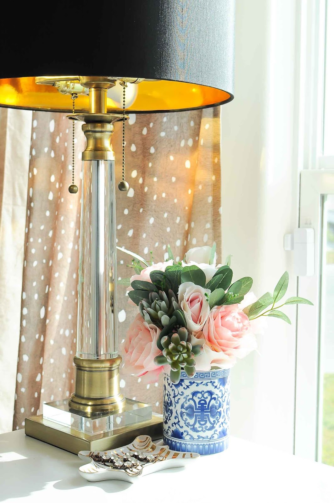 A black and crystal lamp looks gorgeous against a backdrop of fawn curtain panels and a chinoiserie floral arrangement in this chic office space.