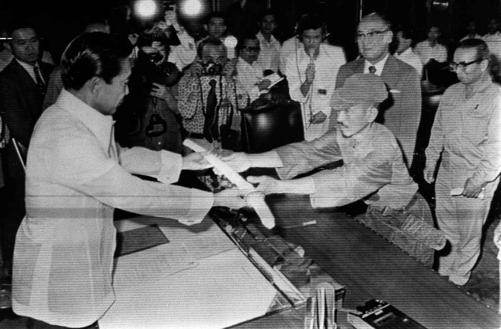 Onoda surrendering his sword to Philippine President Ferdinand Marcos, and received a pardon for his actions over the previous decades (he and his companions had killed some 30 people in their long war).