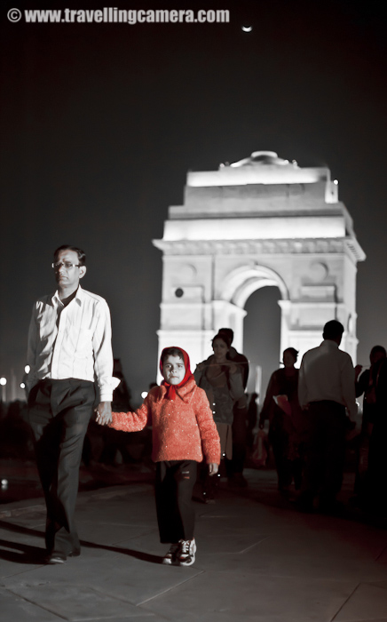 A child holding the father's hand around India Gate in Delhi. There is no better way to discover your city.