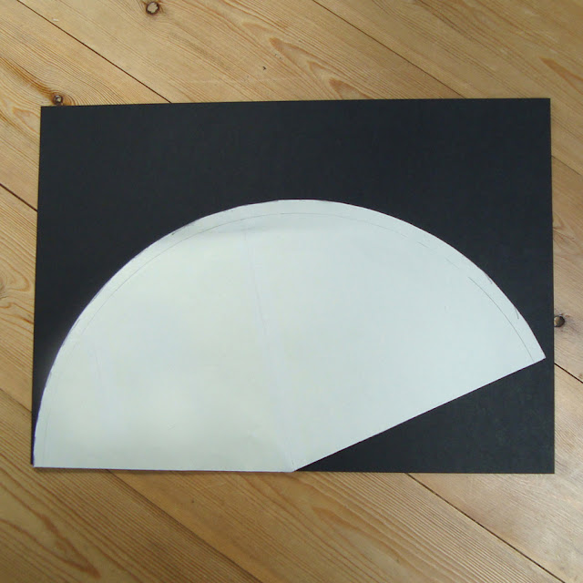 A template for a witches hat placed on A3 black card.