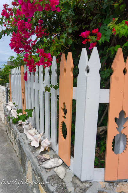 Man-O-War street with cute cut out pineapple fence, shells, and pink bougainvillea