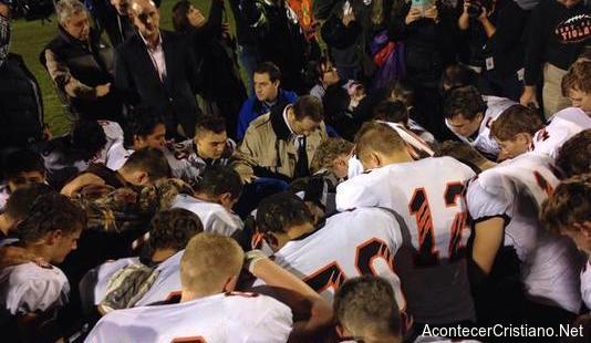 Entrenador y jugadores orando en escuela