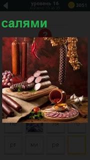 На столе лежат несколько сортов колбасы, среди них имеется салями