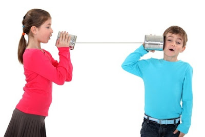 young girl using can and string to talk to young boy