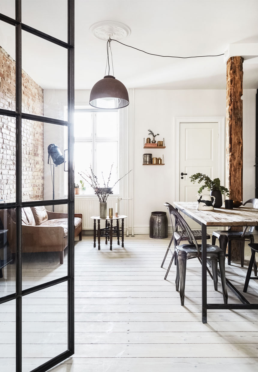 small scandinavian apartment with glass panels, naked bricks and earth tones