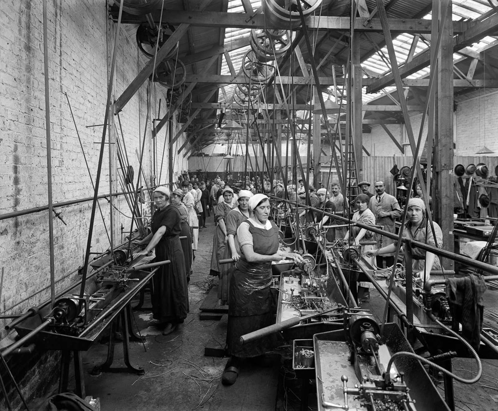 Belgian refugee women use lathes to make ammunition casings at the Belgian Munition Works in London.