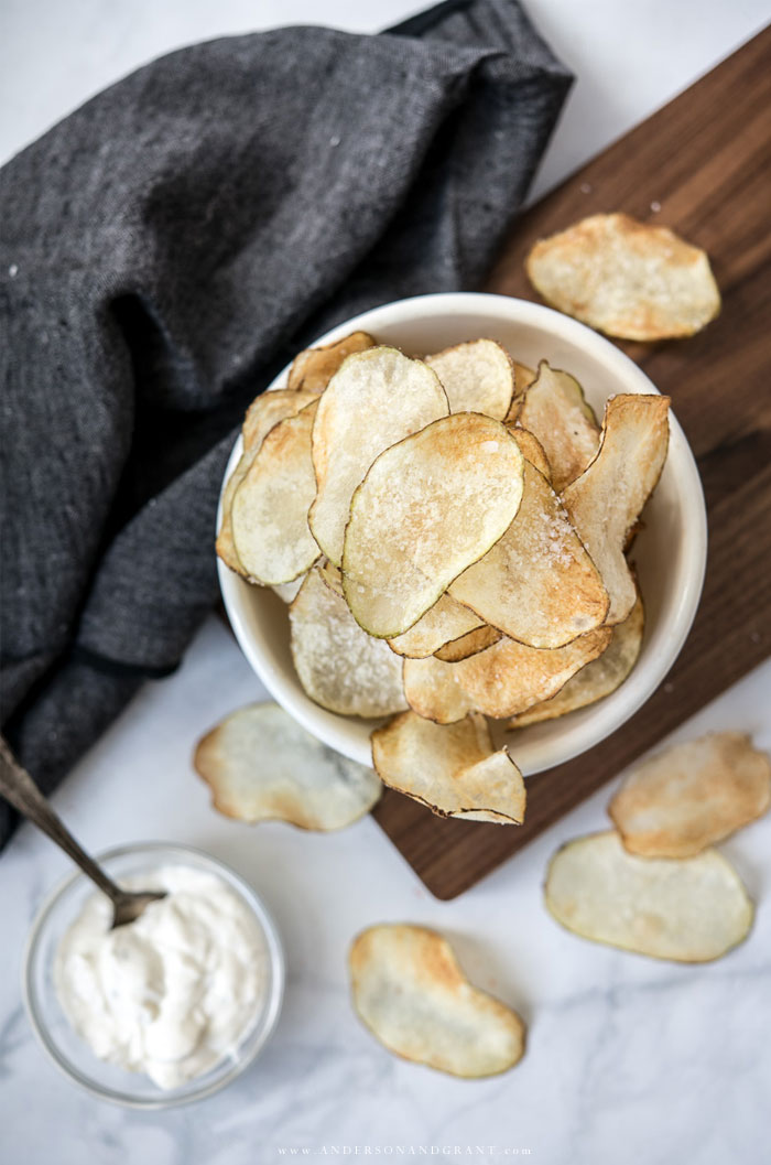 Bowl of salty homemade potato chips and dip on marble countertop