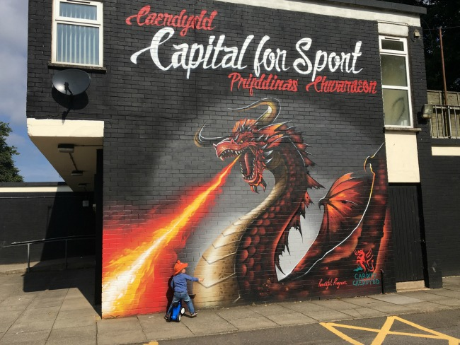 toddler-in-front-of-street-art-a-dragon-breathing-fire-with-capital-of-sport-Cardiff-written-in-English-and-Welsh