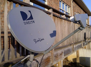 DirecTV satellite dish installed on wood deck