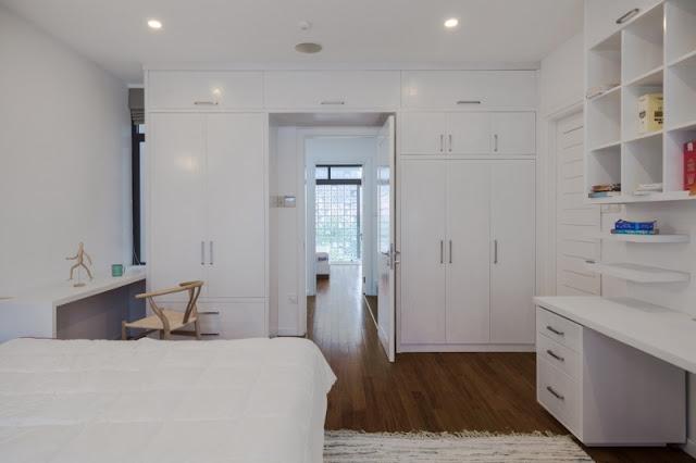 Hệ tủ lớn nhiều ô vuông gắn trên tường phòng ngủ và phòng làm việc