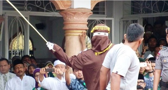 Screenshot VoaIndonesia.com : Algojo pelaksana cambuk mengayunkan rotan ke punggung pelanggar syariah di Banda Aceh, 19 September 2014.