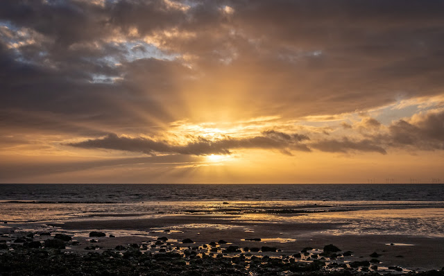 Photo of the sun breaking through the clouds over the Solway Firth just before sunset