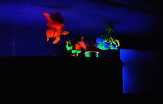 Teatro de luz negra com figuras de peixes feitas em tecido de espuma e pintadas com tinta fluorescente.