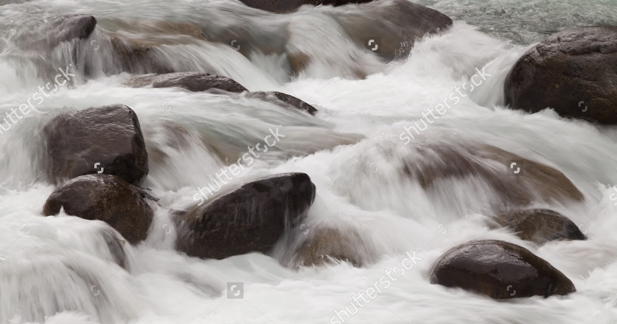 Stock-photo-a-river-blured-and-looking-peaceful-rolling-over-rocks-in-nature-60029642