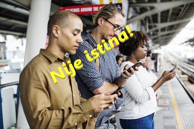 ljudi čekaju voz u grupi, ali svi gledaju u svoje telefone.