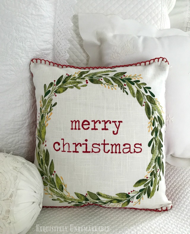 Merry Christmas placemat Pillow DIY on a bed of white pillows