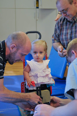 A little girl is fitted for assistive technology