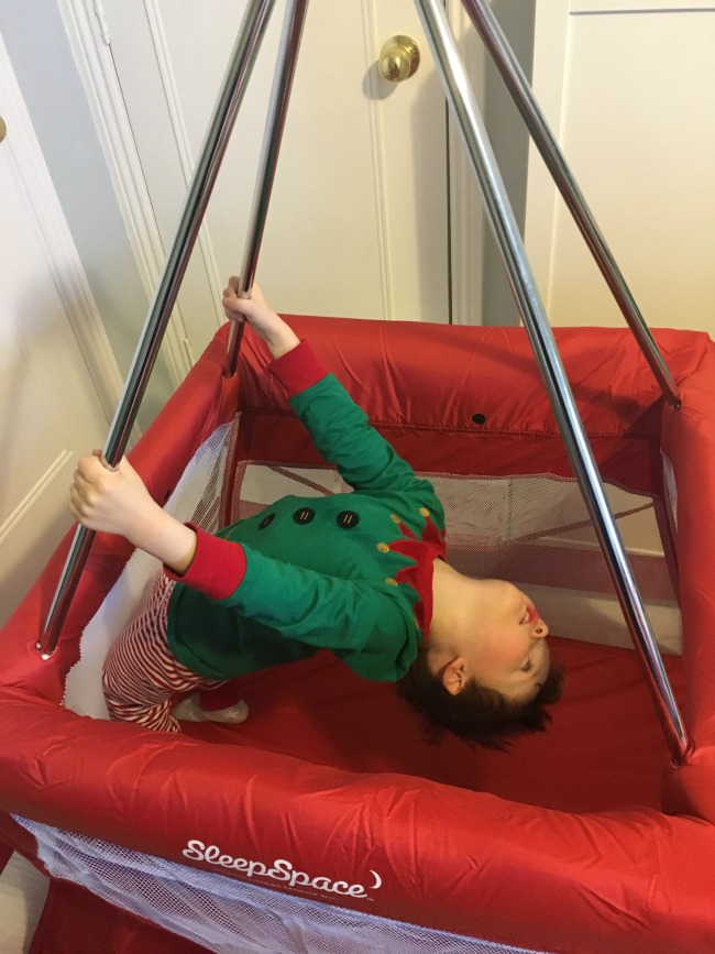 Babyhub-sleepspace-travel-cot-review-child-holding-poles-and-leaning-backwards-in-cot