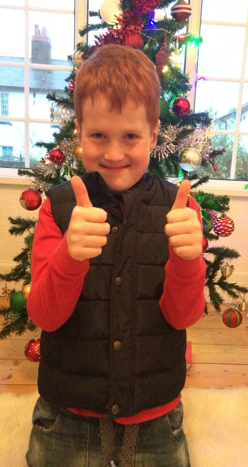 Ieuan giving the thumbs up by the Christmas tree